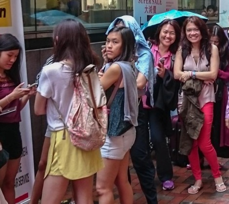 the girls braving a slight drizzle to join in the queue