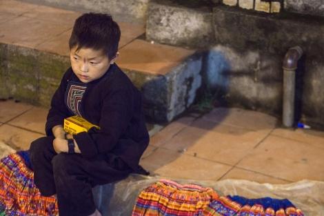 little boy falling asleep over his goods